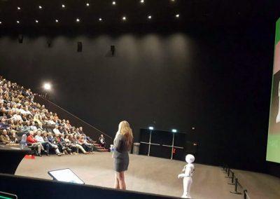 Keynote spreker vrouw met robot in stage, impact robots en exponentiele technologie