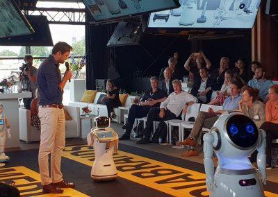 Spreker met robots op het podium